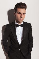 elegant business man leaning on a grey wall