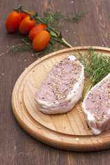 Fresh Raw Steak Meat with spaces, herbs and vegetables on wooden board, selective focus