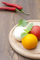 Mozzarella with herbs, fresh vegetables, chilli on a wooden round board, selective focus