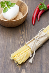 Noodles in paper tied with a rope, a wooden bowl mozzarella, fresh herbs and fresh vegetables on wooden table