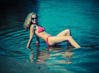 Beautiful young blond woman in a bikini on the beach near the sea