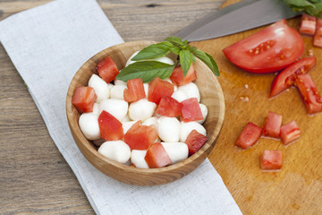Sliced tomatoes, basil and mozzarella cheese on a wooden plate, selective focus