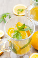 Orange fresh drinks with ice and mint on wooden table, selective focus