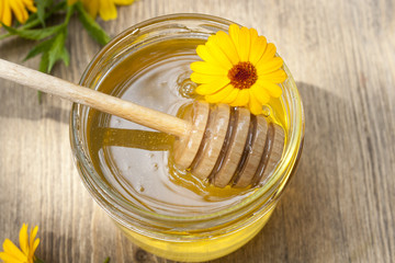Linden honey in jar and calendula blossoms on wooden table, selective focus