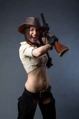 cowgirl with gun on gray background
