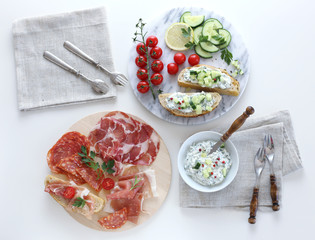 Plate of cold cuts, bread spread and vegetables