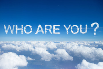"""who are you?"" a cloud word in capital letter on sky over clouds."