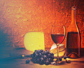 Still-life with cheese, grapes and glass of red wine.