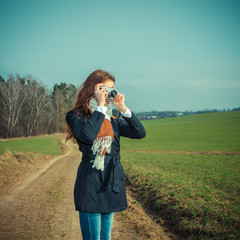 beautiful hipster girl photographer on a warm sunny day. Vintage toning.