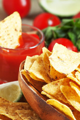 Nachos in wooden bowl with sauce, tomatoes and lime, selective f