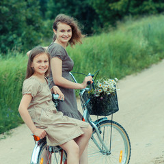 Two hipster girl friends on bicycle having fun. Outdoors, lifestyle. Teenage Girls On Bike