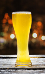 Beer in glass on a wooden table background blur.