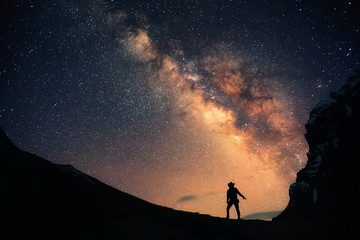 Guardian of the Galaxy. A man is standing next to the Milky Way galaxy and the night sky full of stars.