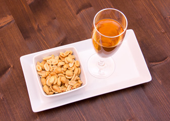 Cocktail and salted nuts on wooden table top