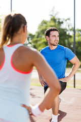 Young athletic man and woman stretching outdoors on a hot summer