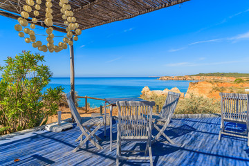 Tables with chairs of restaurant on coast of Portugal near Portimao town, Algarve region Wall mural