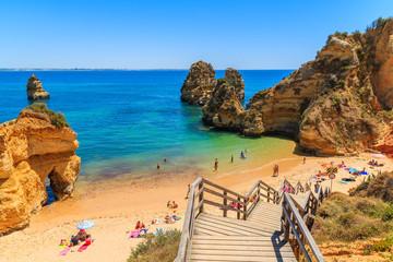 Wooden footbridge to beautiful beach Praia do Camilo, Portugal Wall mural