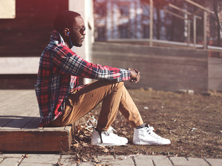 Wall Mural - Lifestyle fashion portrait of stylish young african man listens