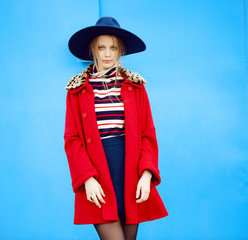 Fashion model in red coat and blue hat poses outdoors