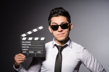 Young man in cool sunglasses holding chalkboard isolated on gray