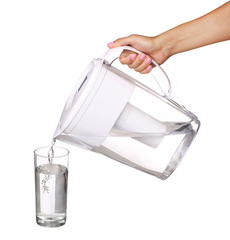 hand holding water filter jug and pouring water into a glass iso