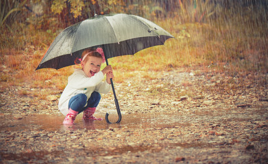 happy baby girl with an umbrella in the rain playing on nature Wall mural