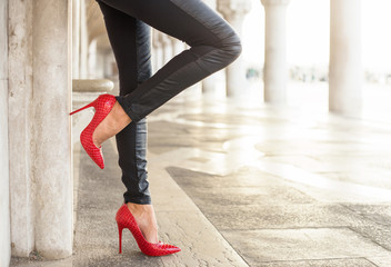 Standing woman in black leather pants and red high heel shoes