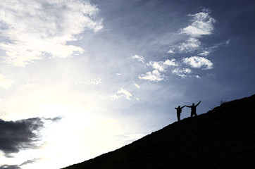 backlight, the man and the woman on the hill, the joy of victory.
