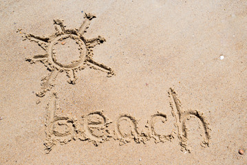 Beach handwritten in the sand of the beach with a lovely sun
