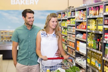 Bright couple buying products in aisle