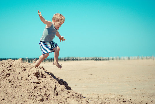 Little boy child jumps from a mountain on the beach
