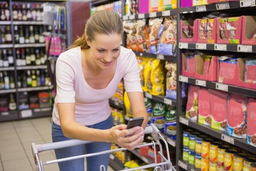 Pretty woman using her smartphone in supermarket