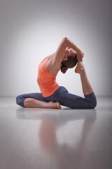 Beautiful sporty fit yogi girl practices yoga asana Eka pada raj