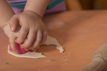 Little chef hands smeary with flour cutting the dough in flower shaped