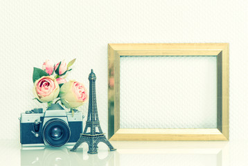 Golden picture frame, rose flowers and vintage camera. Eiffel To