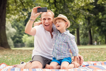 Happy smiling father and son take a self picture with a phone