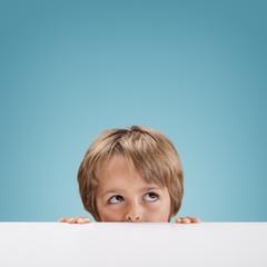 Boy peeking over a white board