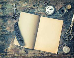 Open book and vintage writing on wooden table. Retro style toned