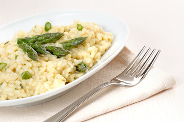plate of risotto with asparagus over a napkin and fork