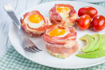 Baked eggs with avocado in bacon cups for breakfast