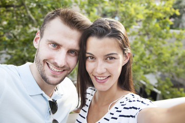 Happy couple taking selfie photo with a camera. Smiling. Vacation concept