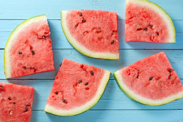 Watermelon slices on blue wood backdrop
