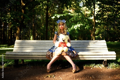 Portrait of young woman dressed as doll sitting on bench