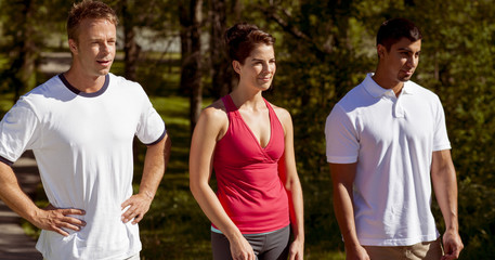 Three athletic friends stand side by side in the park.