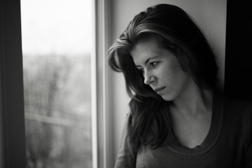 lonely girl near window thinking about something