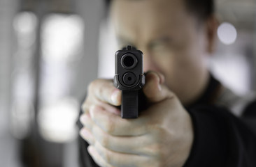 A man aims his semi automatic pistol. Selectively focused on the