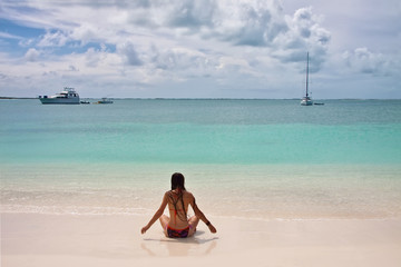 Back view of young woman with super long hair and in swimsuit sitting on white sand beach