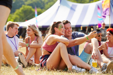 Friends sitting on the grass taking selfie at music festival