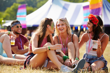 Friends sitting on the grass talking at a music festival
