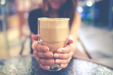 girl holding glass of coffee